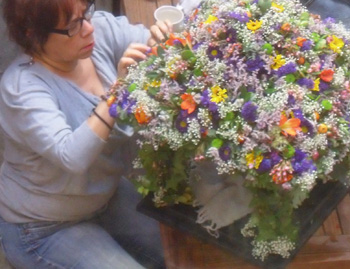 Annette Lorenzo working on the floral canopy for Buddha's Birthday on April 5.